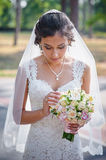 Bride in a white dress in summer green park with a bouquet in hand Royalty Free Stock Images