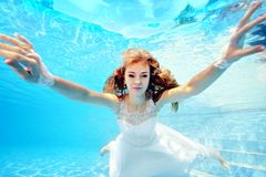 Bride in white dress swims underwater toward the camera. Portrait. Close-up. Horizontal orientation. A view from under the water Royalty Free Stock Photography