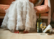 The bride in a white dress took off her shoes and sat on the couch drinking wine Stock Photography