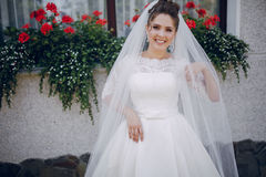 Bride in white dress. And veil, stands at the walls of the house Stock Photography