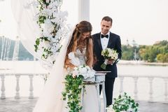 The bride in a white dress at wedding day puts a signature near the arch with a lake on background. Newlyweds stands. Together. Groom with bouquet of flowers Stock Photography