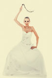 Bride white gown holds black leather flogging whip Royalty Free Stock Photos