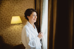 Bride in a white lab coat standing near window Stock Photos