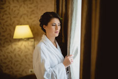 Bride in a white lab coat standing near window Royalty Free Stock Images