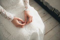 The bride in a white, openwork, wedding dress. The girl`s hands closeup.  royalty free stock images