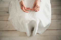 The bride in a white, openwork, wedding dress. The girl`s hands closeup. Copy space stock image
