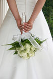 Bride with white roses. A slender bride holding a rose bouquet behind her back royalty free stock images