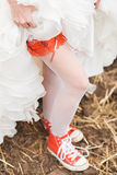 Bride in white stockings in red plimsolls Stock Images