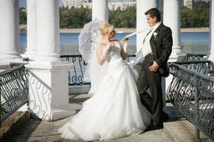 Bride with a white umbrella and  groom Stock Photo