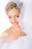 Bride in white veil smiling and looking at camera. Portrait. Fashion wedding shot on a white Stock Photography