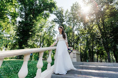 Bride in white wedd dress with bouquet in hand walking down stairs Stock Images