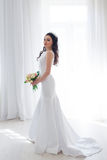 Bride in white wedding dress with a bouquet of flowers Royalty Free Stock Images