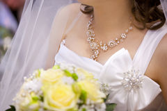 Bride in white wedding dress with bow and pearls, with silver necklace Royalty Free Stock Image