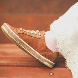 Bride in white wedding dress and brown sneakers or sports shoes. Women`s foot in a sneaker, on a wooden painted bench, close-up, royalty free stock images
