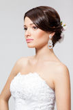 Bride in white wedding dress. Closeup portrait of a beautiful brunette bride with orhid in hairdo and white wedding dress, in studio Stock Photography