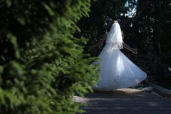 Bride doing pirouette in the park Royalty Free Stock Photo