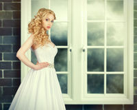 Bride in white wedding dress on a gray background. Portrait of Beautiful Young Fashion Bride in interior.Bride on a background of a window Royalty Free Stock Image