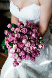 Bride in white wedding dress holding a bouquet. Bride in white wedding dress is sitting and holding a bouquet of roses Stock Image