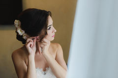 Bride in white wedding dress puts on earring. Royalty Free Stock Images