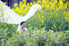 Bride with white wedding dress in rape flower field Royalty Free Stock Image