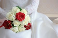 Bride in white wedding dress sitting and holding wedding bouquet Royalty Free Stock Photos