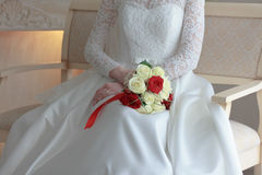 Bride in white wedding dress sitting and holding wedding bouquet Stock Photo