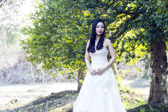 A bride with white wedding dress stand in the middle of trees Royalty Free Stock Image