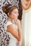 Bride in white wedding dress standing near the window Stock Photos
