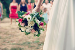 Bride in white wedding dress throws a bouquet of flowers to bridesmaids Stock Photo