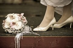 Bride in white wedding shoes stands near the wedding bouquet, vintage photo royalty free stock photography