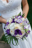 Bride whith natural purple pouquet. Close up of a bride holding a purple bouquet Royalty Free Stock Photography