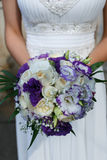 Bride whith natural purple pouquet. Close up of a bride holding a purple bouquet Royalty Free Stock Photos