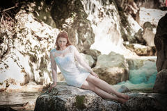 The bride Who Dares. Redhead bride sitting in a mountain brook with her short wedding dress Stock Photo