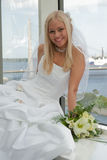 Bride on the window. Beautiful blonde bride with bunch of flowers on the window Royalty Free Stock Photos
