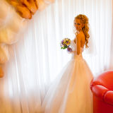 Bride by the window. Fragile bride with a wedding bouquet in the hand is worth a full-length on the background of lush white curtains Stock Image