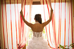 Bride at window. Beautiful bride holding curtains, looking out of the window Royalty Free Stock Photography