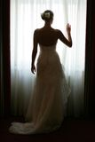 Bride at Window. A full body portrait of a bride in a traditional white wedding dress seen here stoon in her hotel bedroom before the wedding ceremony.She is Stock Image