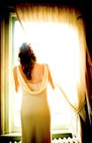 Bride by the window. Bride looking out of the window, observing the arrival of guests Stock Photos