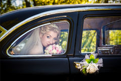 Bride in a window of a wedding retro of the car Royalty Free Stock Photos
