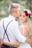 Bride in wine wreathe looks over groom`s shoulder. While he kisses her forehead royalty free stock image