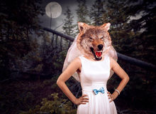 Bride with wolf head in the night wood. Against the moon royalty free stock image