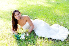 Bride woman lying in park grass Stock Images