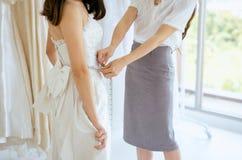 Bride woman trying on wedding dress,Women designer making adjustment with measuring tape. Bride women trying on wedding dress,Women designer making adjustment stock images
