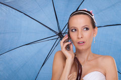 Bride woman with umbrella talking on mobile phone. Stock Images