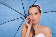 Bride woman with umbrella talking on mobile phone. Stock Photos