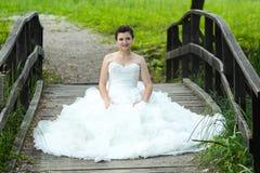 Bride on wooden bridge Stock Photo