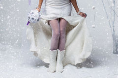 Bride in wool boots. Bride in wedding felted gown holding crystal bouquet. Close-up of female legs in white stockings and wool felted boots. Copy space Stock Photo