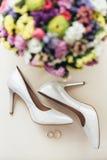 Bride& x27; as sapatas de s estão com um salto nos anéis Imagens de Stock