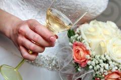 Bride& x27; s handen die een glas champagne en een huwelijksboeket van rode en witte bloemen houden Royalty-vrije Stock Afbeeldingen
