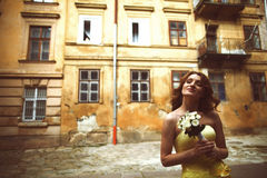 Bride in yellow dress daydreams somewhere in the old city. A Stock Photo